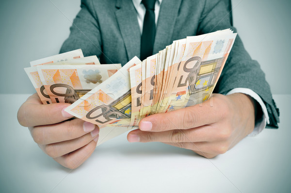 man in suit with counting euro bills Stock photo © nito