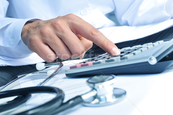 healthcare professional calculating on an electronic calculator Stock photo © nito
