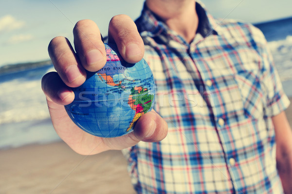 young man with a world globe in his hand Stock photo © nito