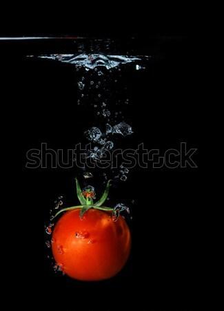 Fresh tomato dropped into water Stock photo © Nneirda