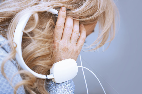 Blond woman listening music via headphones Stock photo © Novic
