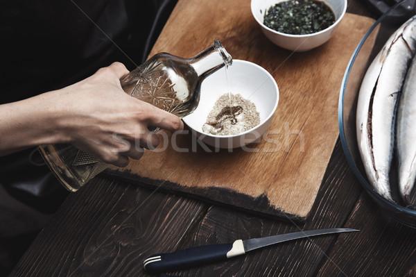 Woman preparing marinade for fish Stock photo © Novic