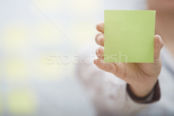 Hand of woman holding sticky note with empty space Stock photo © Novic