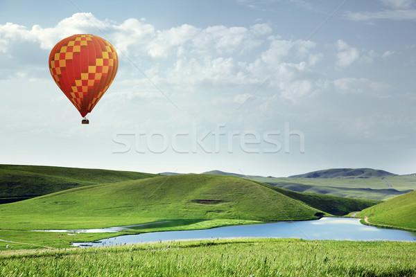 Air balloon flying over the meadows with lake Stock photo © Novic