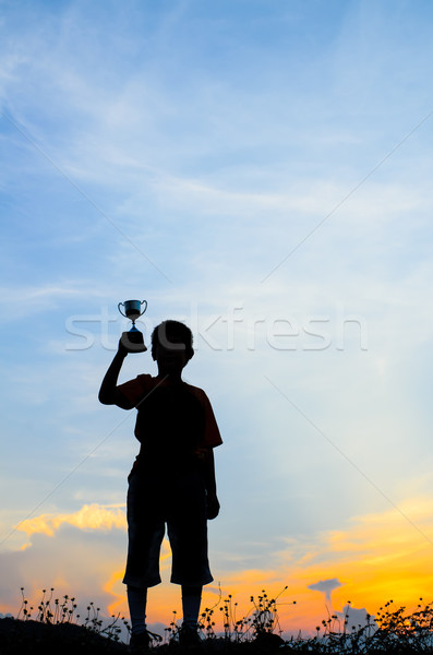silhouettes boy with a cup and sun set natural light. Stock photo © nuiiko
