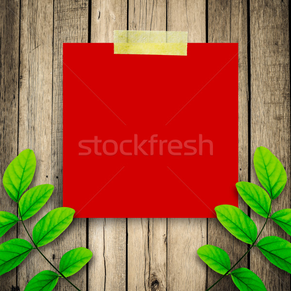Red paper note and green leaves on the old wooden background  Stock photo © nuiiko
