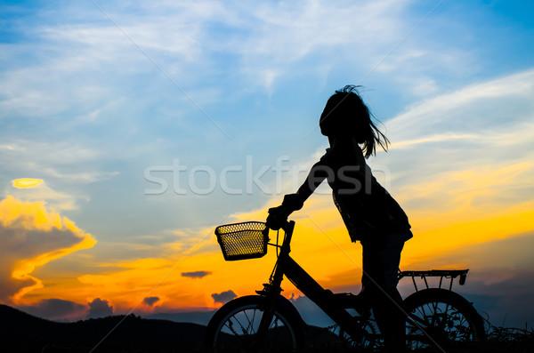 Silhouet gelukkig meisje buiten paardrijden fiets zon Stockfoto © nuiiko