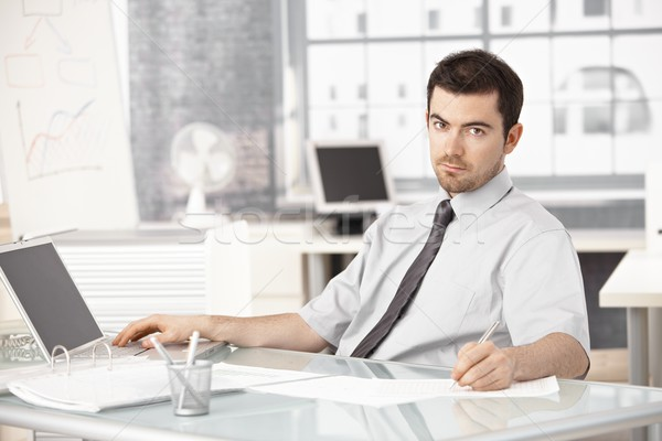 Young businessman working in office using laptop Stock photo © nyul