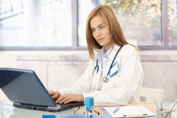Young doctor busy in office using laptop Stock photo © nyul