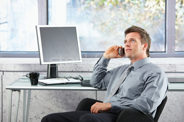 Businessman on call sitting at desk looking up  Stock photo © nyul