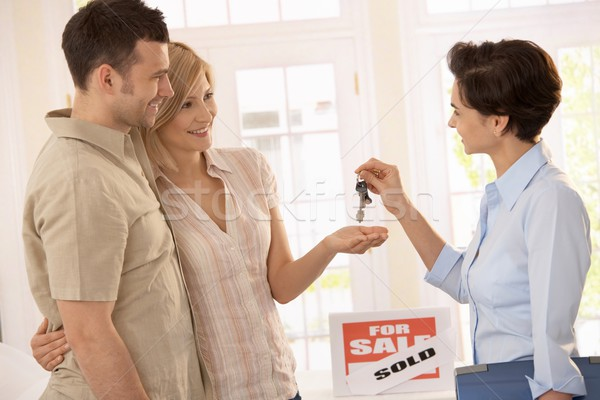 Agent immobilier touches souriant couple femme Photo stock © nyul
