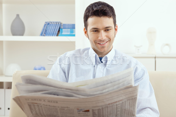 Man lezing krant gelukkig jonge man vergadering Stockfoto © nyul