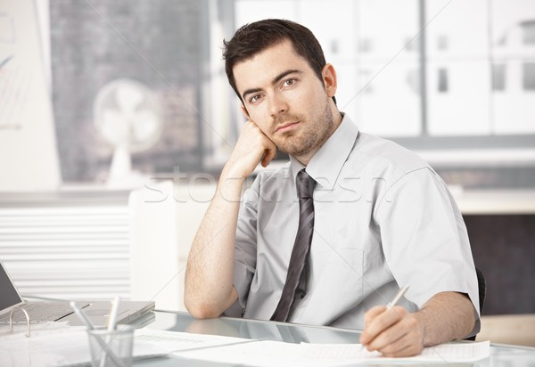 Young man working in office writing notes thinking Stock photo © nyul