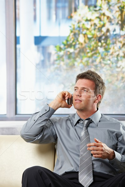 Businessman calling on sofa with gesture Stock photo © nyul