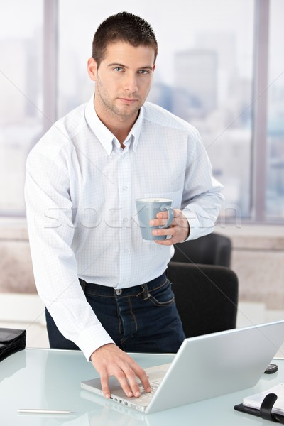 Young casual office worker using laptop in office Stock photo © nyul