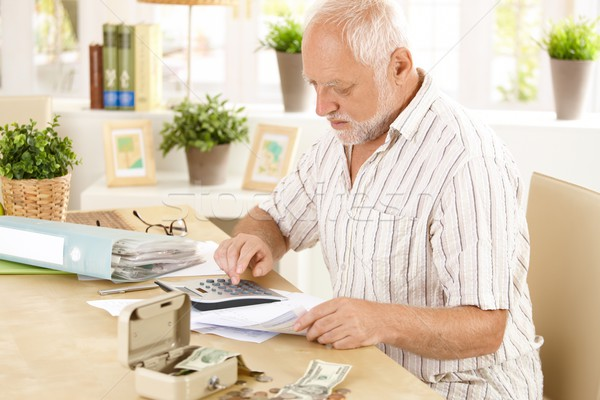 Senior man doing calculation at home Stock photo © nyul