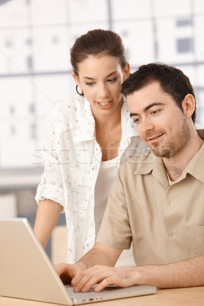 Stock photo: Young couple using laptop together at home smiling