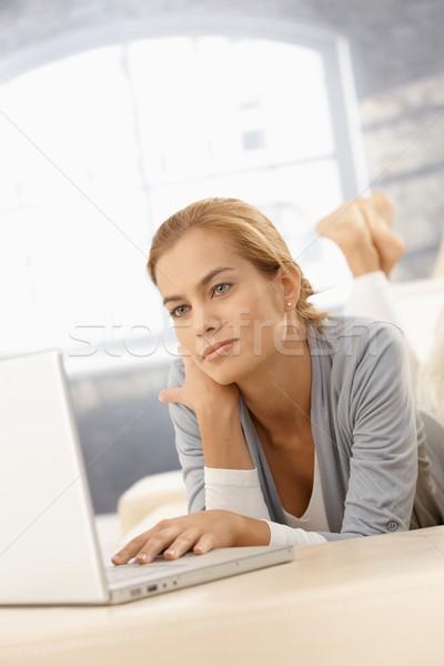Genç kadın dizüstü bilgisayar kullanıyorsanız bilgisayar evde bakıyor ekran Stok fotoğraf © nyul