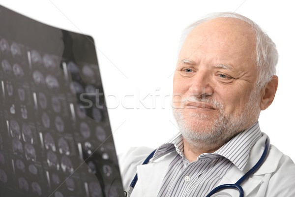 Stock photo: Portrait of senior doctor looking at X-ray image