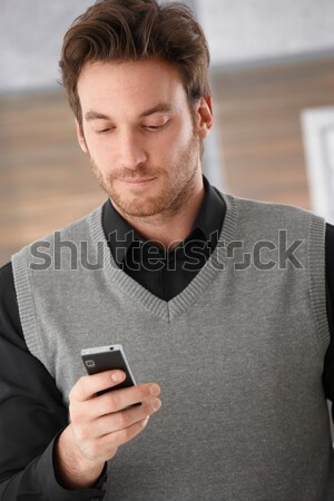 Goodlooking businessman holding mobile phone Stock photo © nyul