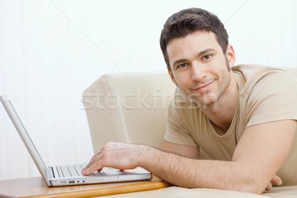 Stockfoto: Man · met · behulp · van · laptop · home · gelukkig · jonge · man · leggen