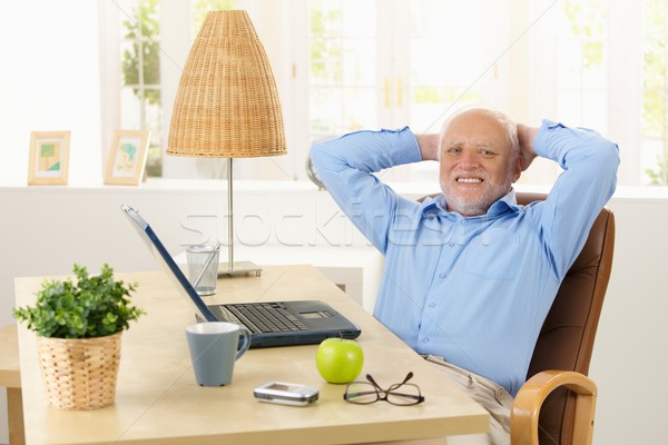 Happy elderly man smiling at desk Stock photo © nyul