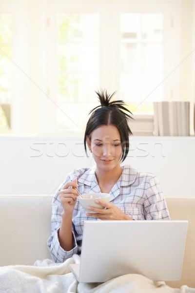 Mujer cereales mirando portátil desayuno ordenador portátil Foto stock © nyul