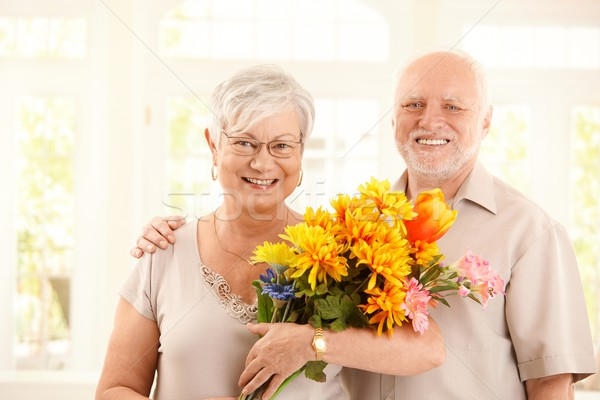 Portrait of happy elderly couple with flowers Stock photo © nyul