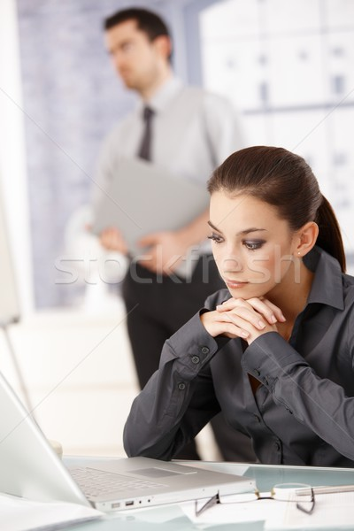 Young woman sitting in office using laptop Stock photo © nyul