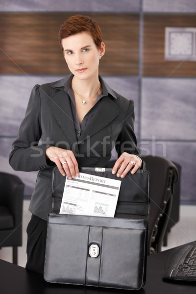 Businesswoman taking document from briefcase Stock photo © nyul