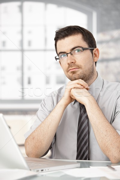 Portrait of young male sitting at desk thinking Stock photo © nyul
