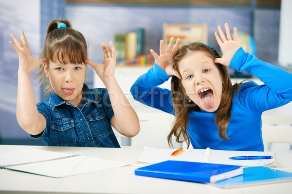 Stock photo: Children sticking tongue in classroom