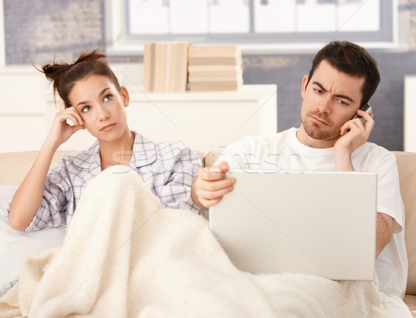Young couple in bed man working woman bored Stock photo © nyul