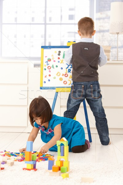 Stock photo: Little boy and girl playing at drawing board