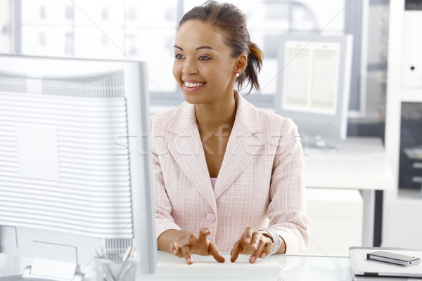Happy office worker girl at desk stock photo © Zsolt Nyulászi ...