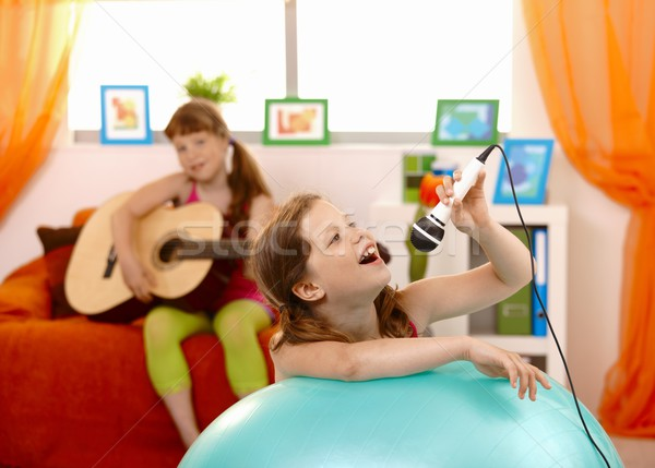 Stock photo: Young girl singing into microphone