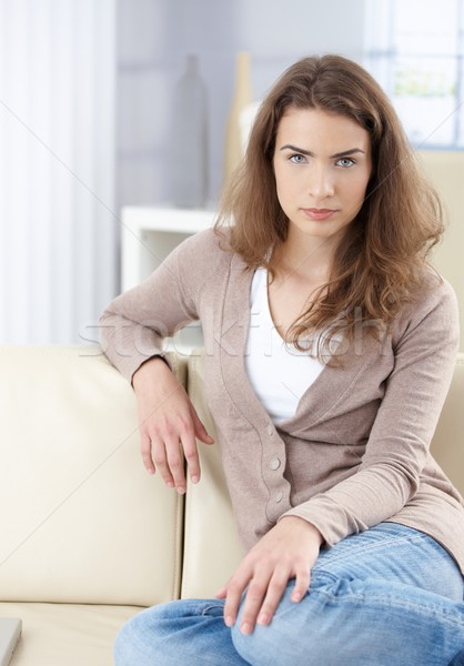 Beautiful woman sitting on sofa at home Stock photo © nyul