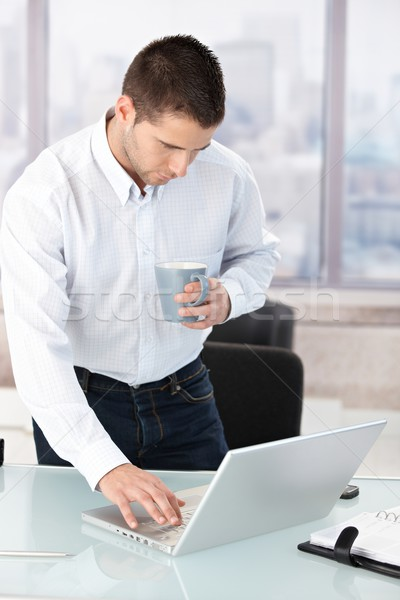 Young man working on laptop in bright office Stock photo © nyul