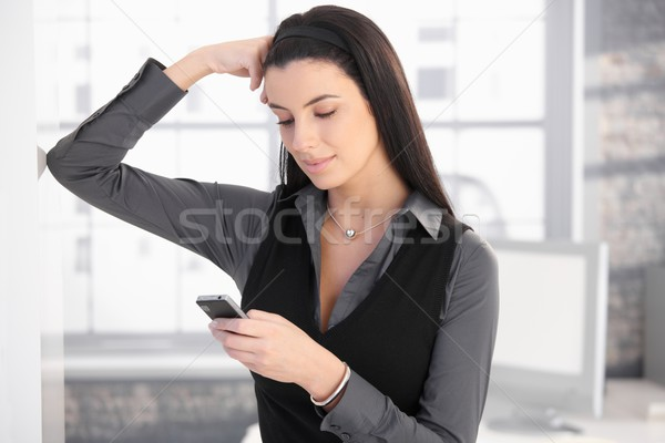 Stock photo: Smiling woman with mobile phone