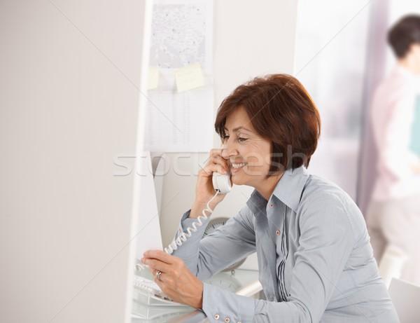 Mature businesswoman talking on landline phone Stock photo © nyul
