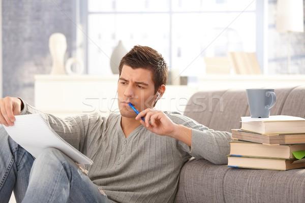 Egyetemi hallgató tanul otthon tart jegyzetek toll Stock fotó © nyul