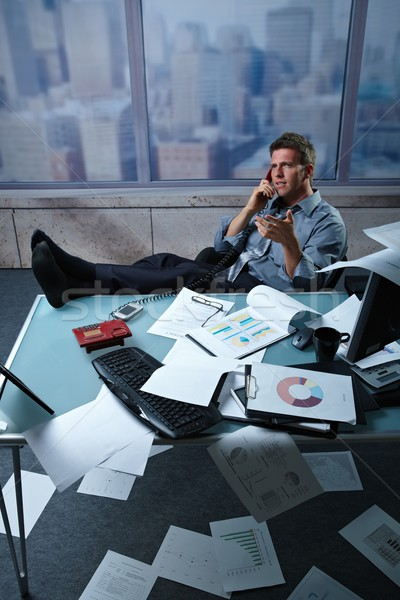 Businessman on call feet up papers all around Stock photo © nyul