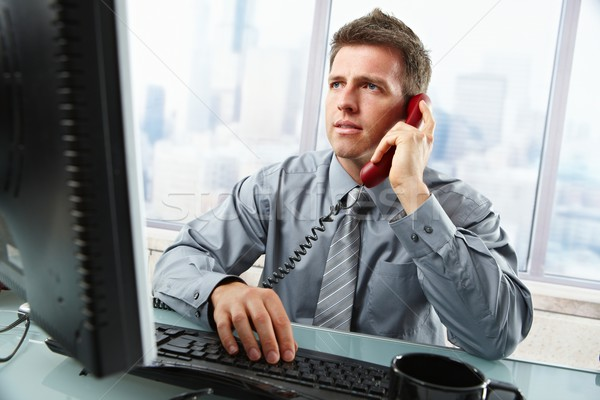 Businessman talking on landline phone in office Stock photo © nyul