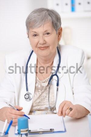 Stock photo: Senior doctor writing notes