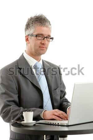 Empresário escrita notas em pé mesa de café isolado Foto stock © nyul