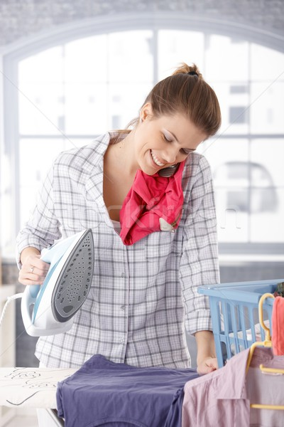 Happy woman talking on phone while ironing Stock photo © nyul