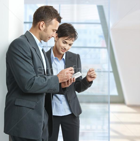 üzletemberek mobil kettő áll iroda lobbi Stock fotó © nyul