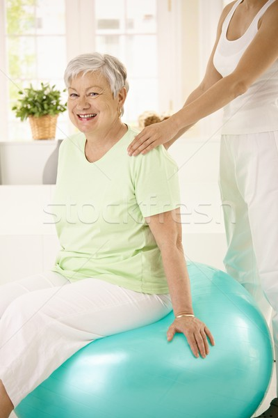 Personal trainer assisting senior woman Stock photo © nyul