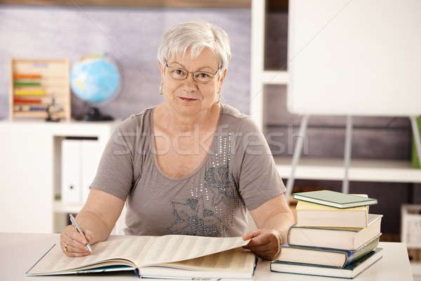Senior teacher in school searching in a book Stock photo © nyul