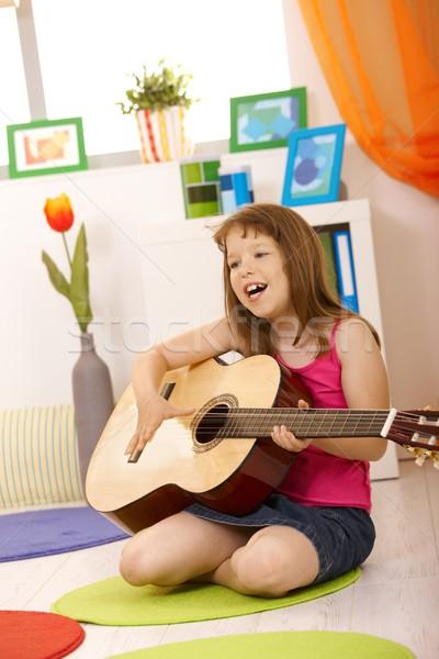 Portré iskolás lány gitár énekel ül nappali Stock fotó © nyul